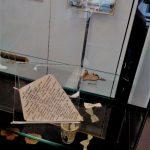 Dans la vitre « Musée des épaves » : plusieurs supports naturels inhabituels, ayant provoqué l'impulsion de l'écriture, en l'occurrence, un cerf-volant de papier et sa ribambelle de nœuds papillons